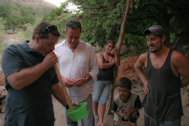 Pedro Quintanilla, center, watches his business partner Alejandro Martinez Grey sipping mezcal through a siphon. The mezcalero, or mezcal producer on the right has just just finished distilling the mezcal.