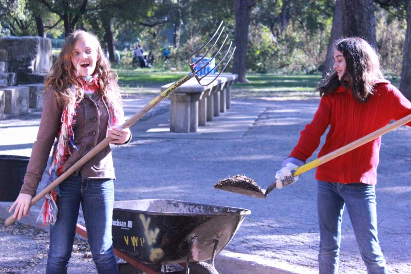 Laura Blydenburg (red) and friend Shelbie Hendrick have a little fun while shoveling mulch.