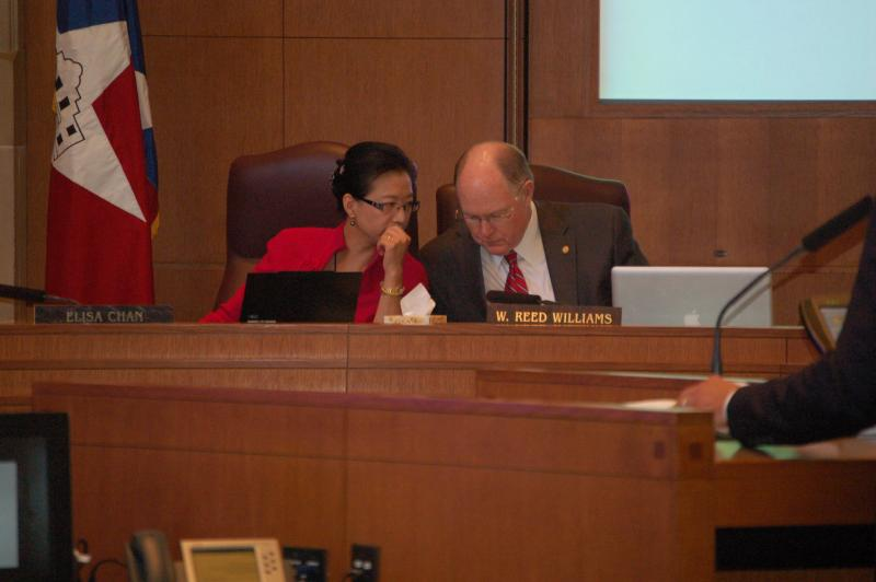 Council members Elisa Chan and Reed Williams lean in closely to discuss an issue at the August meeting where the city council voted to send the Pre-K 4 SA measure to voters in November