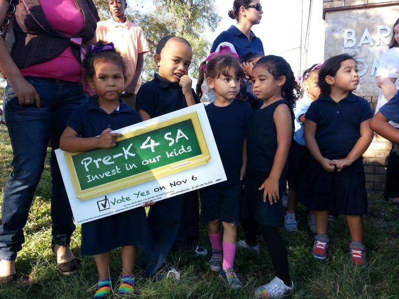 Children from the George Gervin Academy hold signs during a press conference of community leaders on the east side in support of Pre-K 4 SA