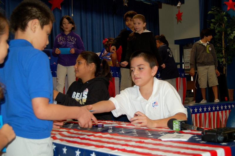 Fernando Mares helps a student receive a ballot before voting in the Fenwick Elementary mock election.