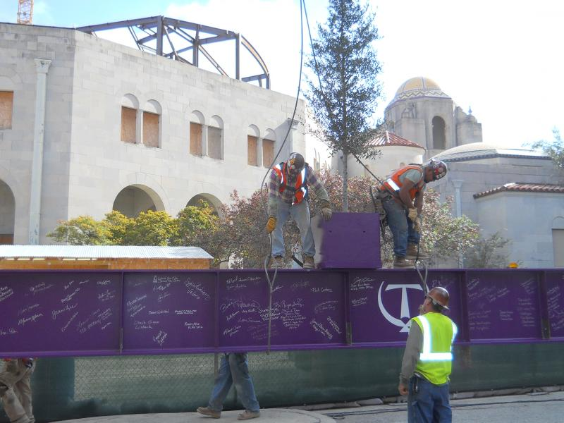 Construction workers involved with the Tobin Center secure a 5-ton steel beam to crane to be lifted. The resting Live Oak tree will be planted on the center's grounds.