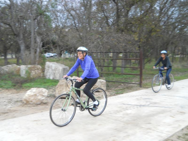 Two cyclists enter the South Leon Creek Greenway.