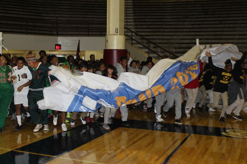 Ten athletes from each of the district's middle and high schools break-through the banner at the start of the ceremony.