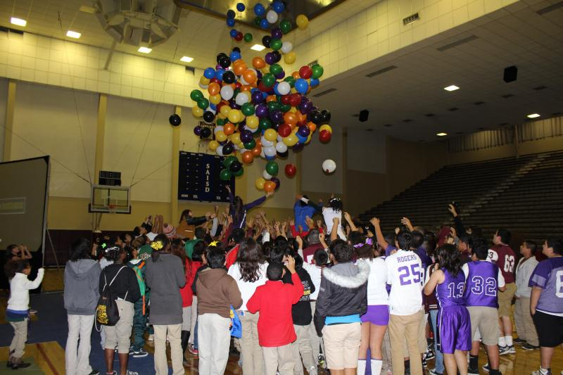 Balloons drop from the ceiling of the Convocation Center onto the students.