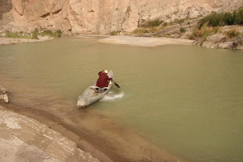 A Mexican citizen paddles his canoe from the northern shoreline of the Rio Grande into Coahuila, Mexico near Boquillas