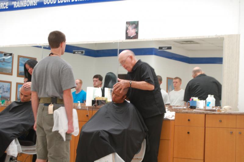 West instructs trainees how to line up to quickly cut their hair so they can move on to receiving their uniforms