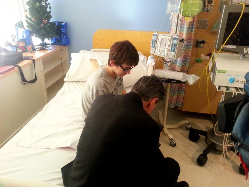 Archbishop Gustavo prays with 16 year old Jordan who is undergoing treatment at Christus Santa Rosa Hospital