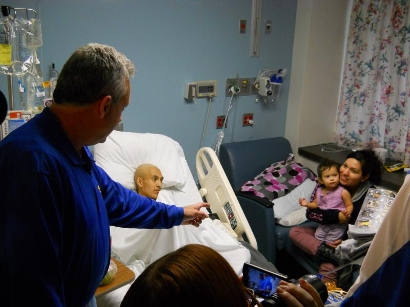 Coach Jim Zeleznak offers a basketball to the 11-month old daughter of oncology patient Johnny Gonzalez at University Hospital.
