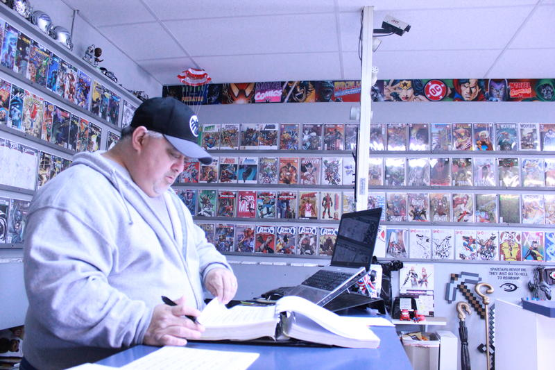 Pete Contero does the books while surrounded by comics and graphic novels.