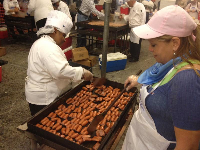 Kelly Diggs of St. Philip's College (left) and Gina Renobato prepare some of the 10,000 sausages that will feed the thousands of people attending