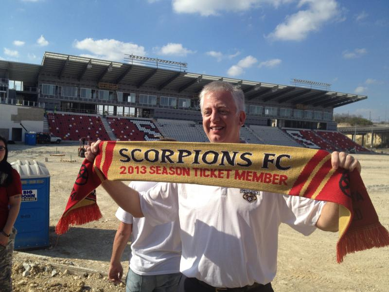 Gordon Hartman - founder of Soccer for a Cause - holds a up a soccer scar reserved for season ticket holders. Emblemed scarves are often by soccer players to show support for thier team.