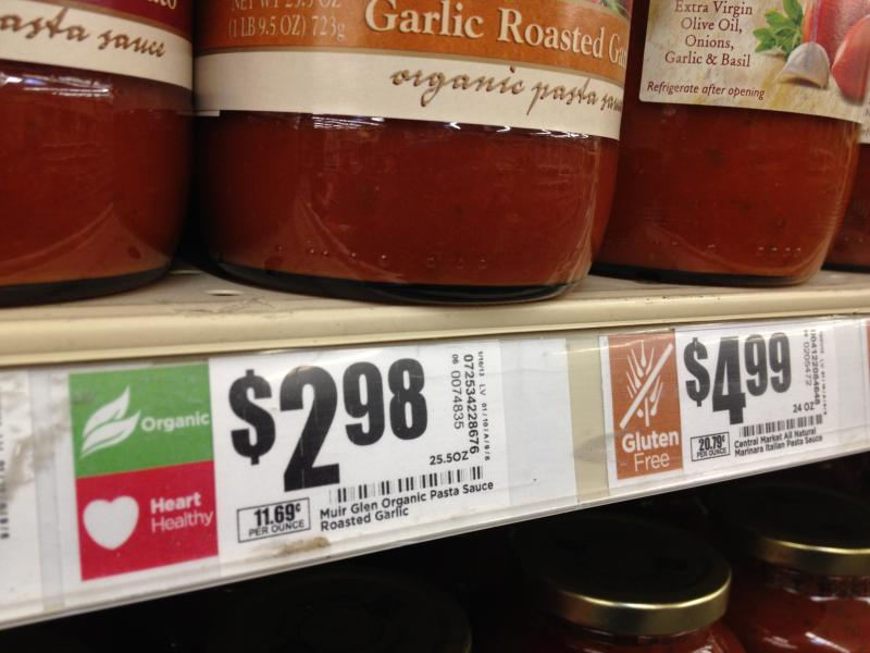 "New nutrition labels depicting ""Heart Healthy"" and ""Organic"" are displayed near the price of tomato sauce in one of the store's aisles."