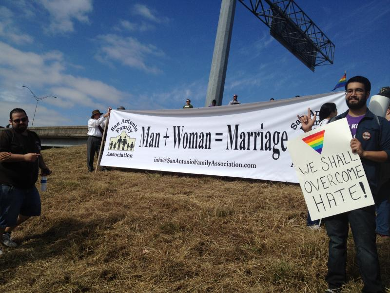 "The San Antonio Family Association holds a banner depicting ""Man + Woman = Marriage."" David Cisneros of the Human Rights Campaign holds a sign of his own in protest."