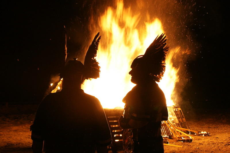 Two members of the Jarl's squad, dressed as Vikings, are silhouetted in front of the burning galley at Up Helly Aa.