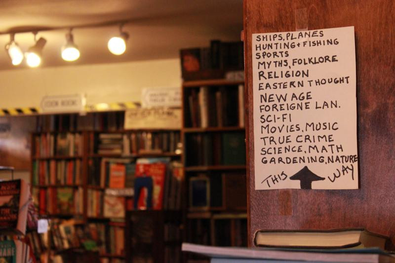A hand written sign directs customers further back into the rooms that are more like small caves, the walls lined with books from floor to ceiling.