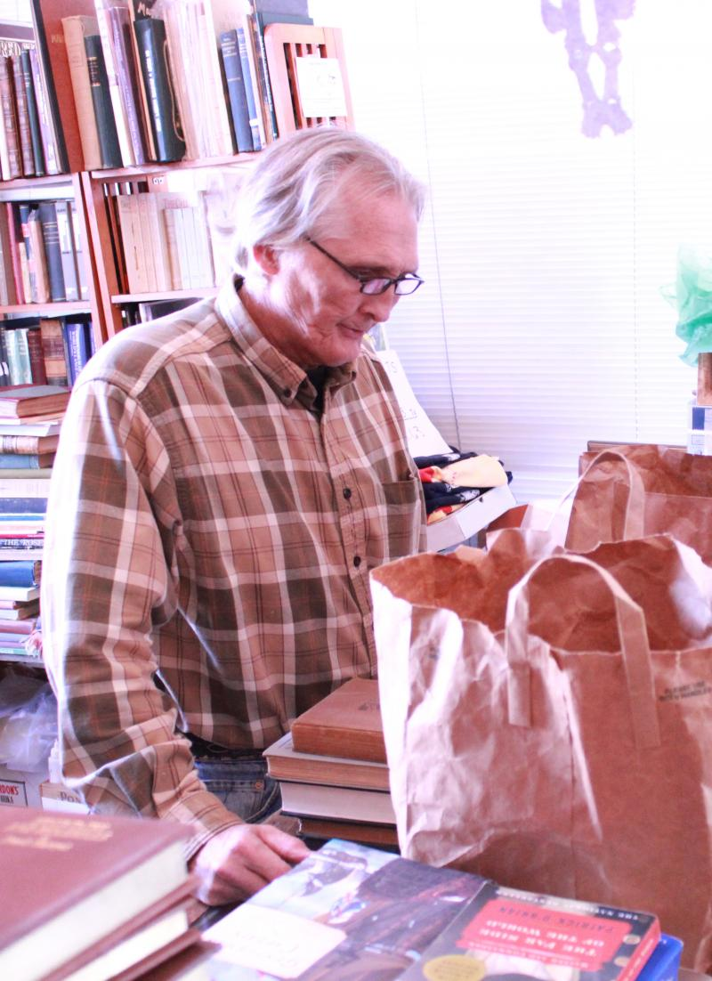 Manager John Peace takes a careful look at each item brought in to be sold by customers. Of the bags brought in on this occassion, he didn't buy any books.