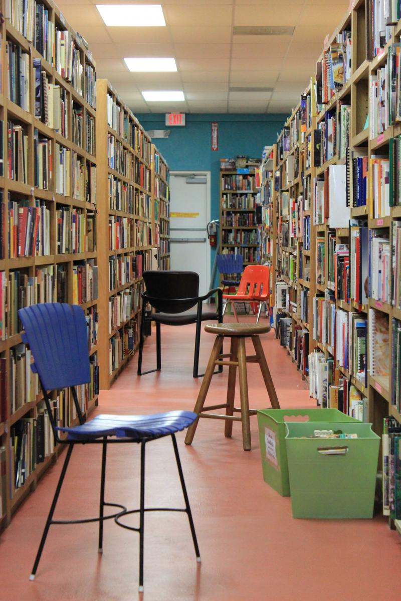 Chairs line each of the long aisles of books for people to comfortably browse for titles.