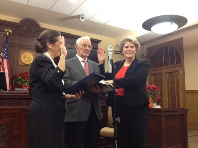 Susan Pamerleau sworn in by former County Judge Cyndi Krier with Pamerleau's father holding the Bible