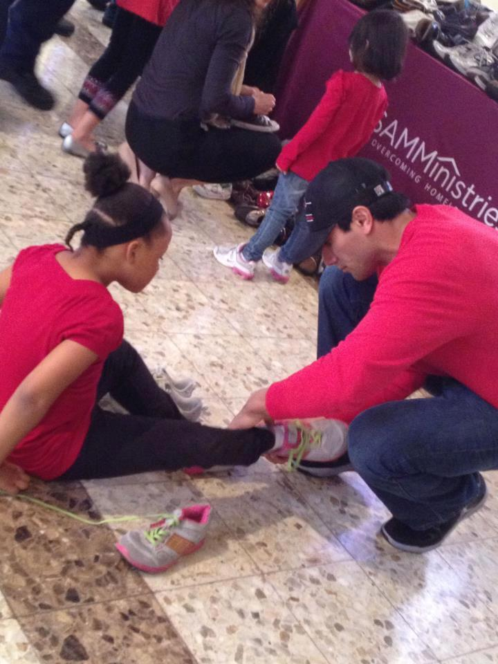 "Eric Castillo helps a girl at SAMMinistries try on a pair of ""new"" shoes"