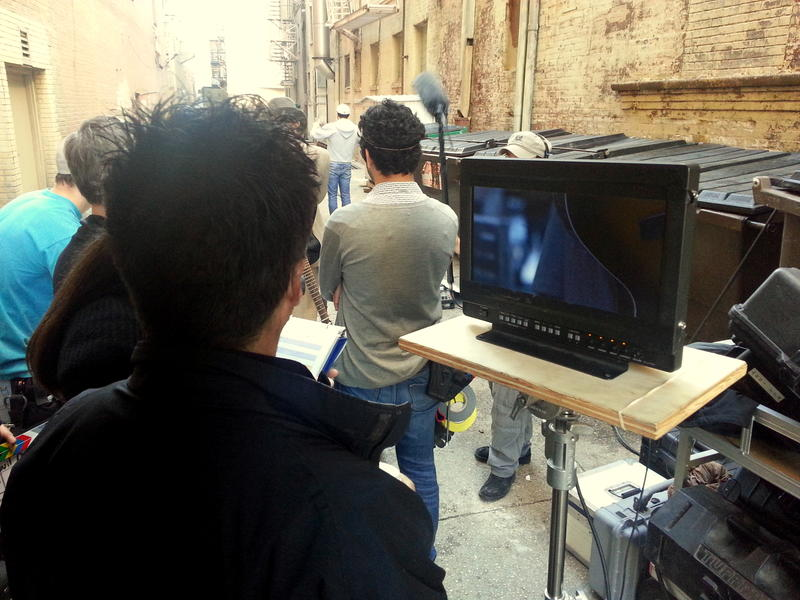 Writer and director Robert Brink looks at a monitor to set a shot during filming.