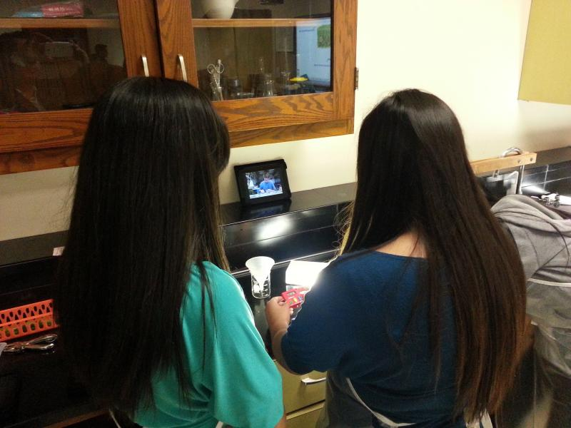 Marina Garcia works on a biology lab with a classmate using a Kindle tablet