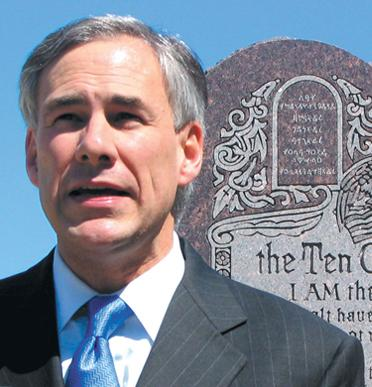 Abbott in front of stone tablets displaying the 10 Commandments on the grounds of the state capitol.