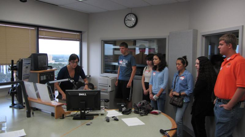 Morning Edition host Crystal Chavez explains the KSTX studio to Camp KPAC students.