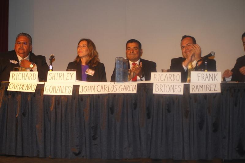 Candidates answer questions in front of an audience at a debate at the Guadalupe Arts Cultural Center.