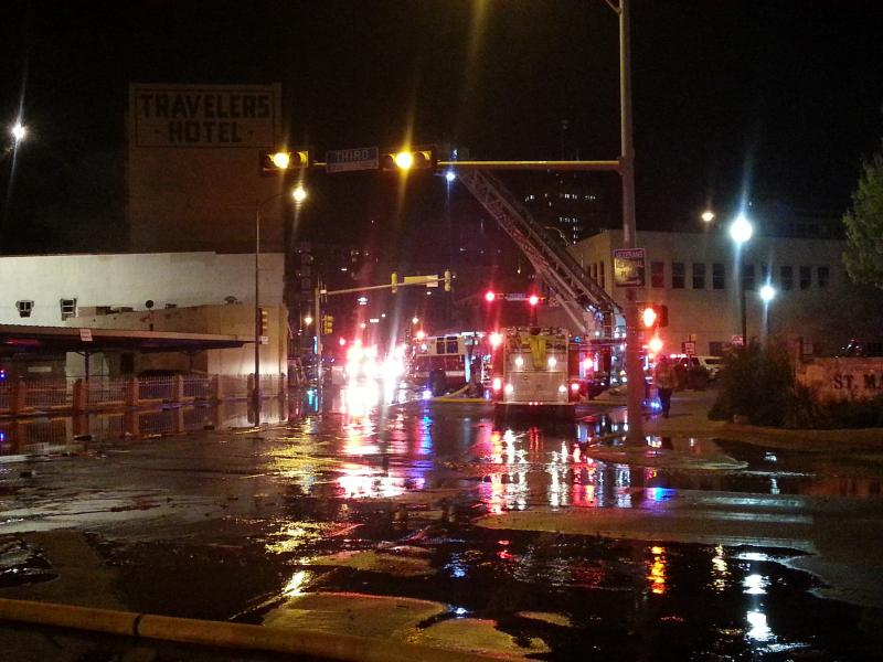 Water flows down Broadway as firefighters battle the two-alarm fire at an empty building downtown.