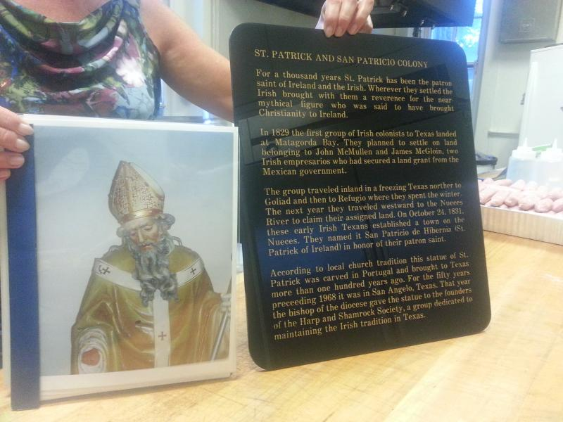Carolyn Dowd holds up a picture of the 300 year old St. Patrick to be restored by the Harp and Shamrock Society of Texas