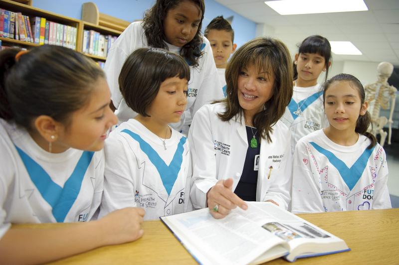 Radiologist Darlene Metter, M.D., (second from right) of UT Medicine San Antonio, shows a photo of an X-ray to fifth-graders at a local elementary school on National Doctors' Day 2011.
