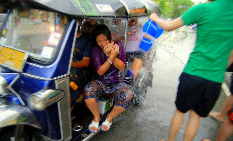 People in a tuk-tuk get targeted during the Songkran festival in Chiang Mai, Thailand