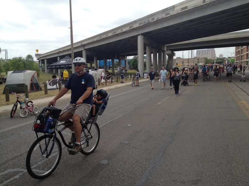 A cyclist rides down Broadway underneath IH-35.