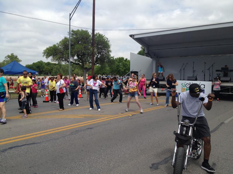 A group of people participate in Zumba at a reclovía just outside of Lion's Field.