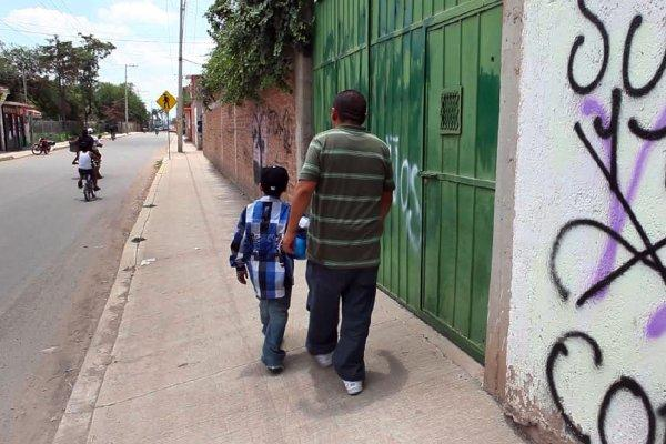 An American boy walks down a street in Guanajuato, Mexico with his father, a deported Mexican national.