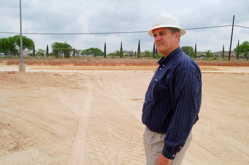 Project manager Chuck Smith stands outside the southside model education center, located at Brooks City Base, near where the playground will be constructed.
