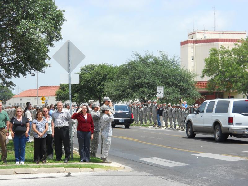 Members of JBSA Air Force and civilian personnel salute the family of Capt. Mark Voss as they leave the Kelly Field Flight Line in San Antonio.