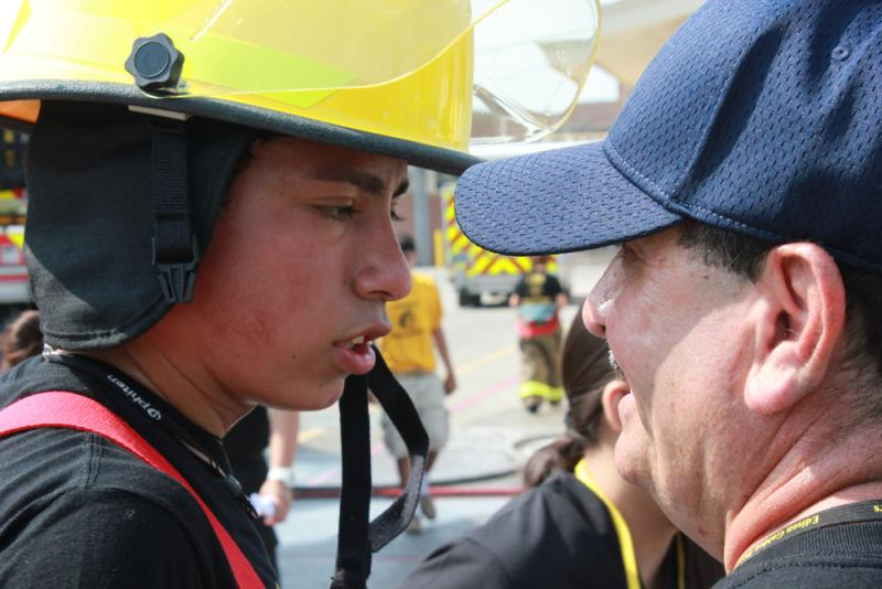 A fire cadet gets some instruction mid exercise.