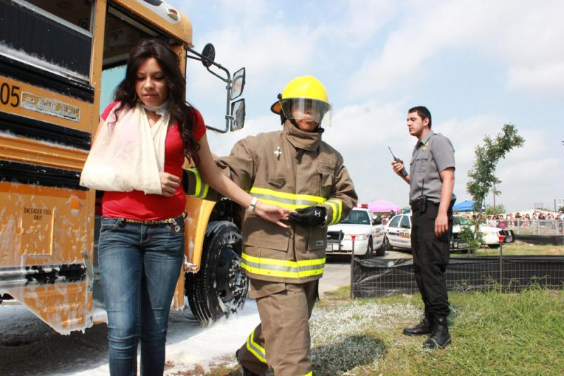 "Fire cadet escorts an ""injured"" girl from the bus."