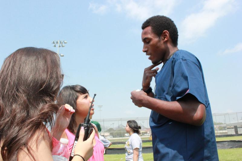 "A medical student briefs the PIO students on the extent of the fire fighter's ""injuries."""