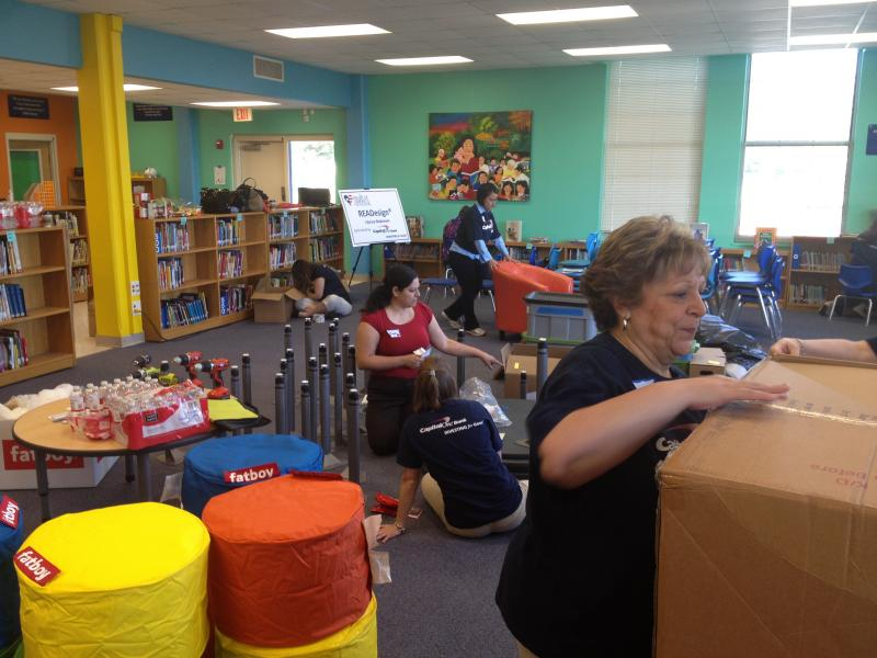 Volunteers with Capital One begin assembling the chairs and tables for the library.