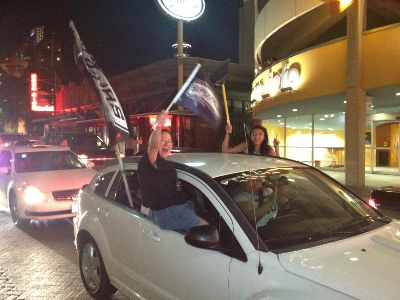 Spurs fans hang outside of their vehicle in celebration of the sweep