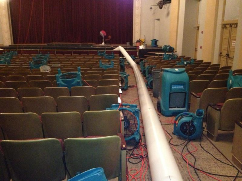 Fans blow hot air to evaporate the water-logged carpet.