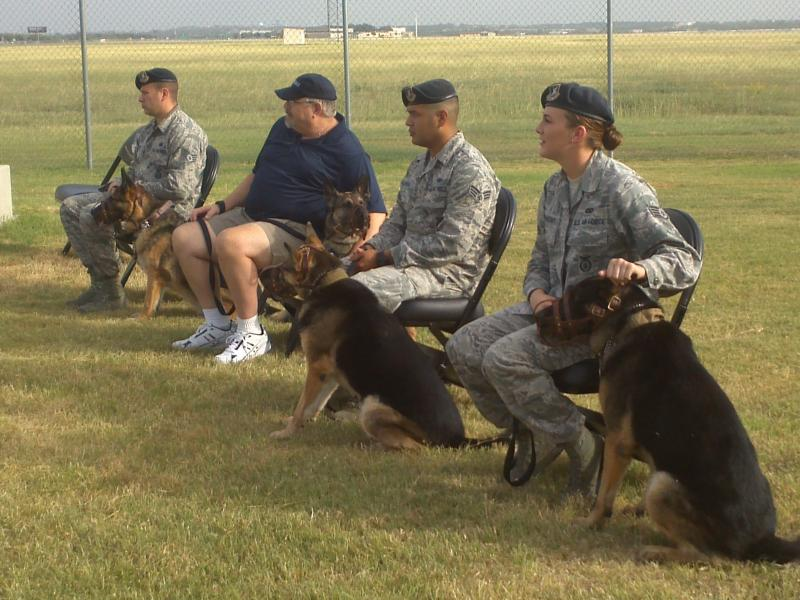 Military Working Dog Handlers with their new family members, (L-R) MWDs Teri, Kevin, Harry, and Leo