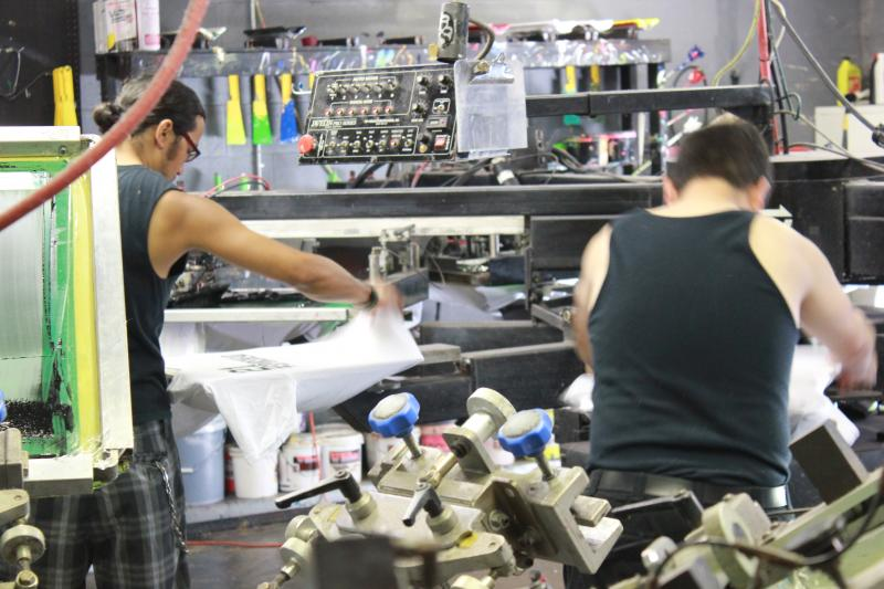 Employees at Ace Screen graphics pull shirts off the line.