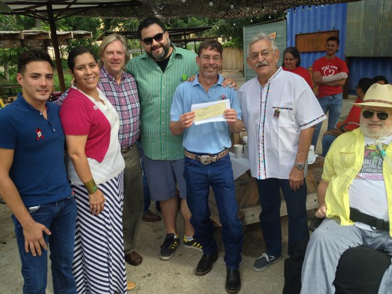 Robert Rehm (right) is joined by Cornyation Corridinator Ray Chavez, SAAF Executive Director David Euhel, Set Designer Jesse Mata, Cornyation President Tom McKenzie et  al in the check presentation to the San Antonio AIDS Foundation.