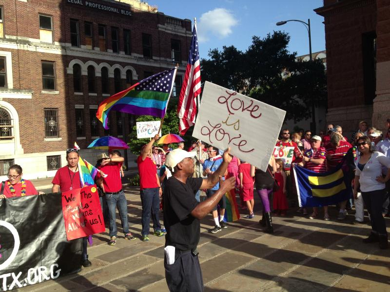 """A man holds a sign that reads """"Love is love"""" at a pro-gay rally outside the Bexar County Courthouse."""