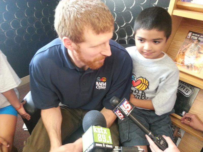 Matt Bonner reads to children at the new learning center at Wheatley Middle School.