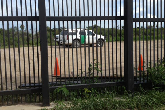 U.S. Border Patrol vehicles near the border fence.